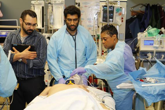 Chris Sharkey (left), a language interpreter, Dr. Ravi Patel, an emergency medicine resident and Felicia Davis, a respiratory therapist, attend to an emergency room patient at Truman Medical Centers. Credit: Truman Medical Centers